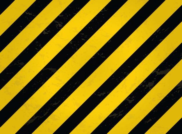 黒と黄色の縞模様。グランジ警告縞模様の背景。