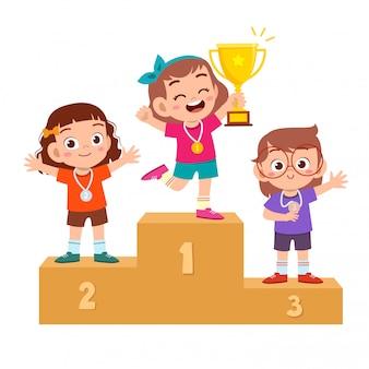 幸せなかわいい子供がゲームゴールドトロフィーを獲得