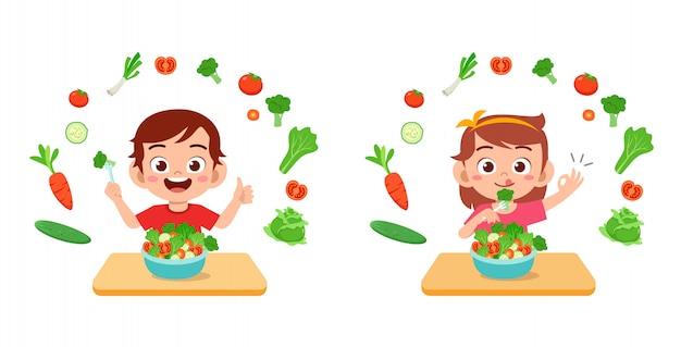 Симпатичные счастливые дети едят салат из овощей и фруктов