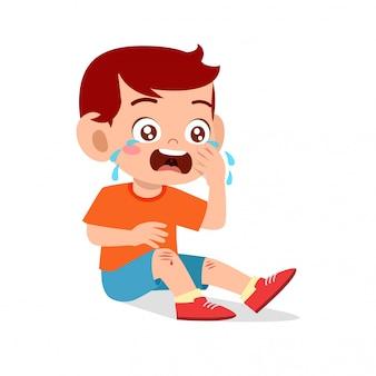 悲しい泣くかわいい子供の少年の膝の傷の出血