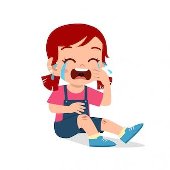 悲しい泣くかわいい子供の女の子の膝の傷の出血