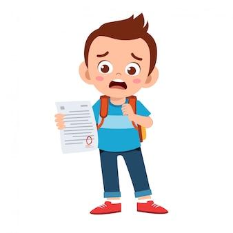 悲しい子供の少年は試験から悪い点を持っています