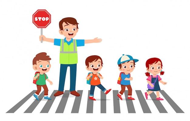 幸せな良い男は子供たちが道路を横断するのに役立ちます