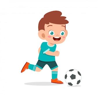 Милый малыш мальчик играет в футбол как нападающий