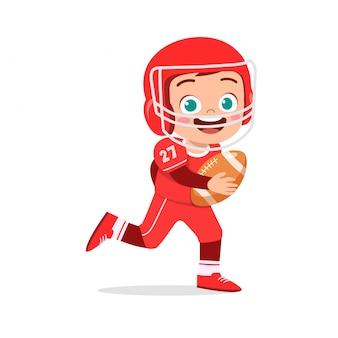 幸せなかわいい子供男の子がアメリカンフットボールをプレイ