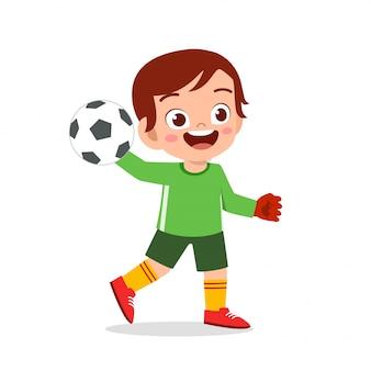 Счастливый малыш мальчик играть в футбол вратарь