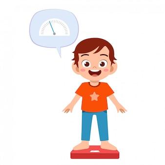 幸せなかわいい少年は体重計を使用