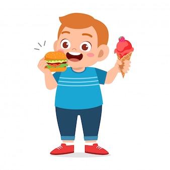かわいい太った子供の少年はジャンクフードを食べる
