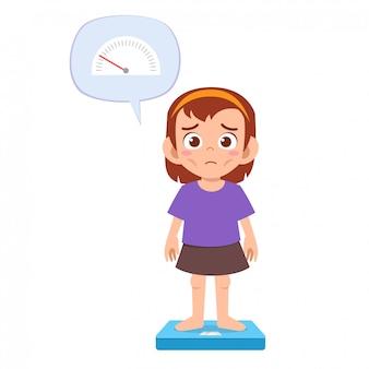 スキニー悲しい子供の女の子は体重計を使用