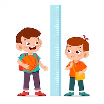 幸せなかわいい男の子が一緒に高さを測定