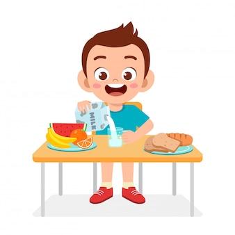 幸せなかわいい子供男の子は健康的な食べ物を食べる