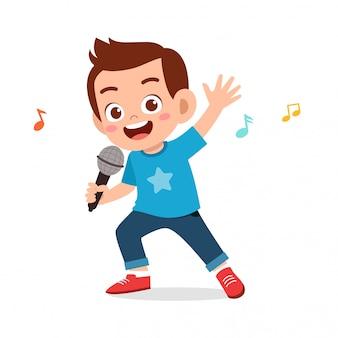 幸せなかわいい子供男の子が歌を歌う