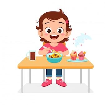 Счастливая милая девушка ребенк ест здоровую еду