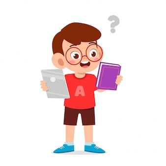 幸せなかわいい子供男の子は電話と本の間で選択します