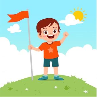 幸せなかわいい子供男の子は山の上の旗を運ぶ