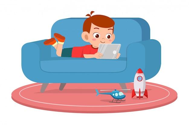 幸せなかわいい子供男の子がソファーでタブレットを使用してください。