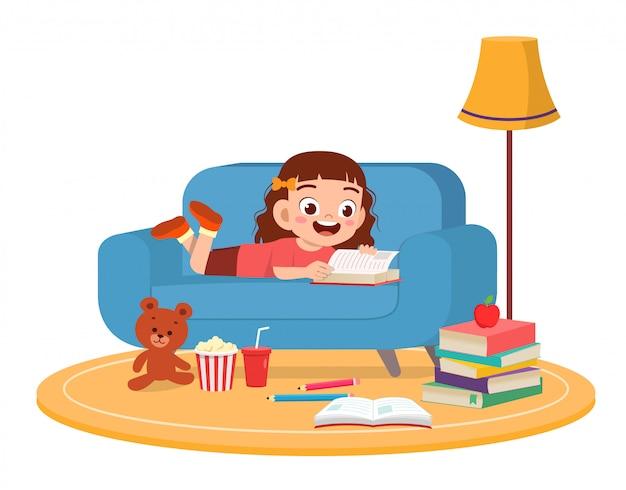 幸せなかわいい子供の女の子がソファーでスマートフォンを使用します。