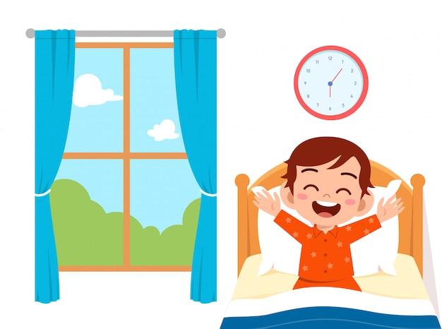 幸せなかわいい子供男の子は朝に目を覚ます