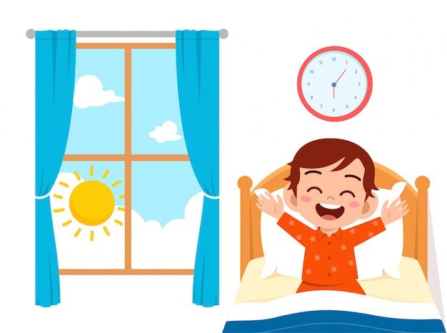 幸せなかわいい子供男の子が目を覚ます