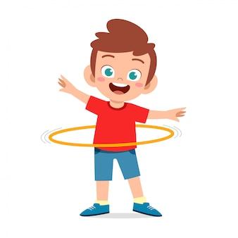 幸せなかわいい子供男の子プレイフラフープ