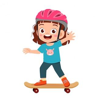 Счастливый милый маленький ребенок девочка играть скейтборд