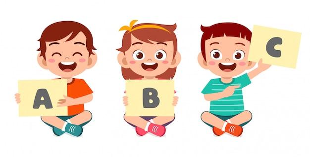 Счастливые милые маленькие дети мальчик и девочка учат алфавит