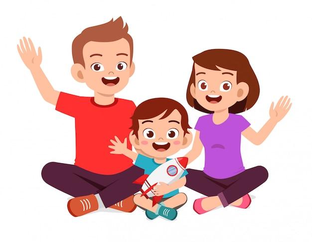 幸せなかわいい子供男の子はママとパパと一緒に座る