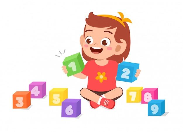 Счастливый милый маленький ребенок девочка играть с номером блока