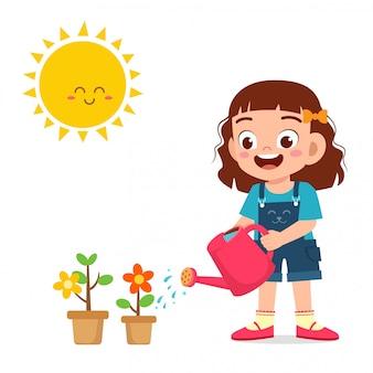 Счастливая милая маленькая девочка поливает цветок