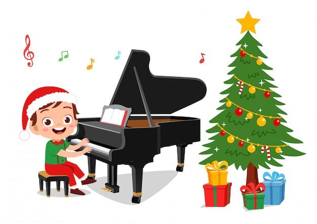 Счастливые дети поют под пианино на рождество