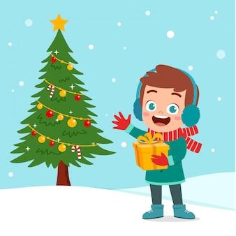 幸せな子供のクリスマスツリーの雪