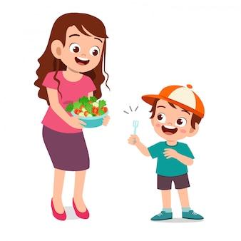 Милый счастливый малыш ест салат из овощей фруктов
