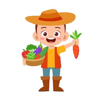かわいい幸せな子供は果物や野菜を収穫します