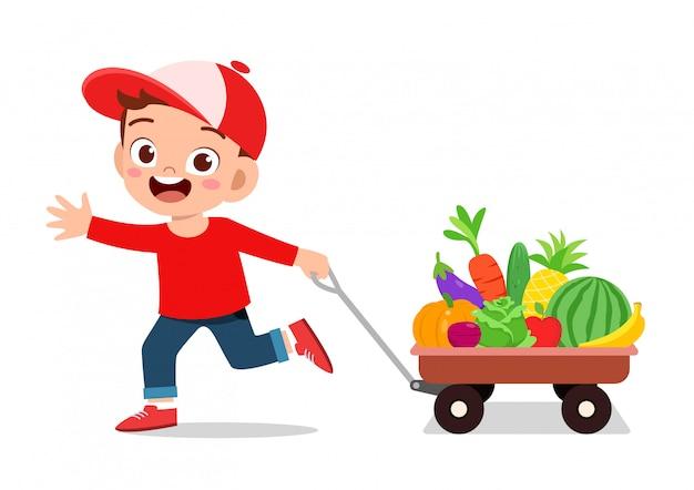 Милый счастливый ребенок покупает фрукты и овощи