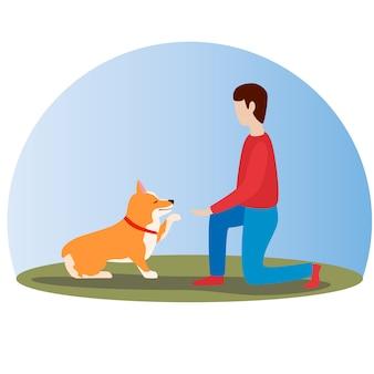 男は彼のウェールズのコーギー犬を訓練します。幸せなかわいい犬。ウェールズコーギー。子犬が座って足をします。