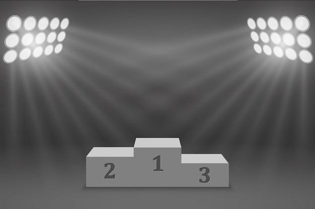 サーチライトで照らされたスポーツの勝者の台座の表彰台