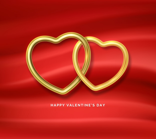 Счастливого дня святого валентина. две золотые сердечки соединены между собой на красной шелковой ткани.