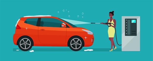 アフロの女性がセルフサービスの洗車で車を洗う