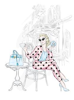 세련된 옷을 입은 아름다운 소녀가 카페에 앉아 있습니다.