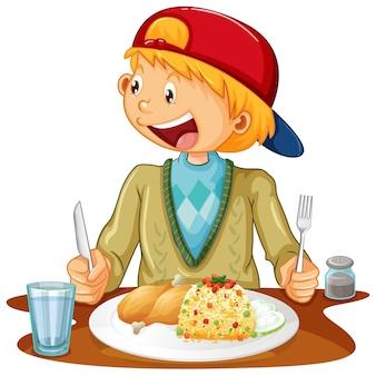 白い背景の上のテーブルで食事をしている少年