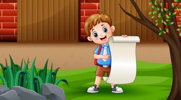 Мальчик держит бумажный рулон под деревом