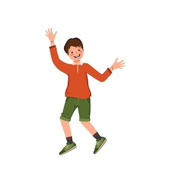 셔츠 반바지와 운동화를 신은 소년이 춤을 추거나 점프하며 행복한 미소를 짓고 있는 아이가 얼굴을 가진 십대를 기뻐합니다.