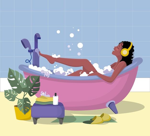 Брюнетка в ванне с пеной слушает музыку и подпевает своей любимой песне.