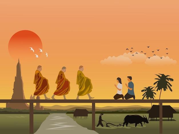 僧侶が木造の橋を歩いており、男性と女性が礼拝に座っています。パゴダと朝の空を背景に水牛で畑を耕している農民。