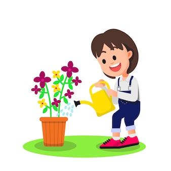 쾌활한 어린 소녀가 꽃에 물을 준다