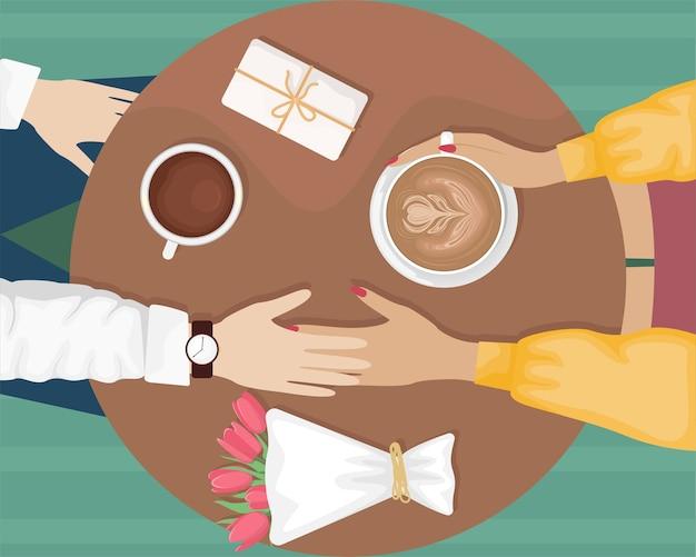 Влюбленная пара сидит за столиком в кафе и держится за руки