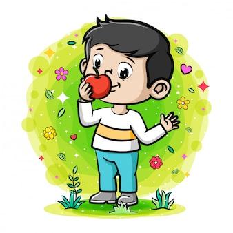 Милый мальчик ест яблоко в саду
