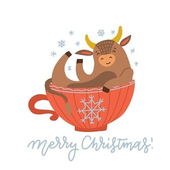 Милая корова сидит в красной чашке. новогодняя атмосфера.