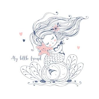 かわいい人魚が岩の上に座って、ヒトデを手に持っています。