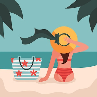 수영복과 모자를 입은 소녀가 모래 해변에 앉아있다. 비치 가방, 여행, 휴가